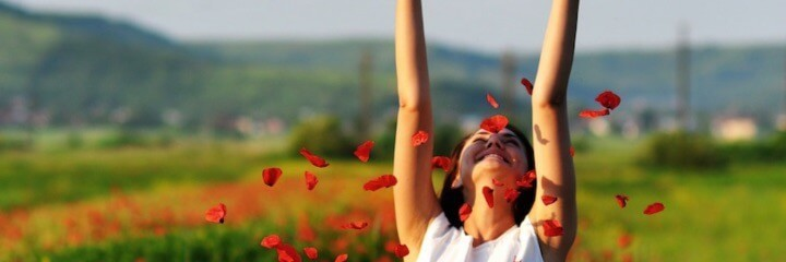 woman stands on field raising hands feeling fulfilling in life
