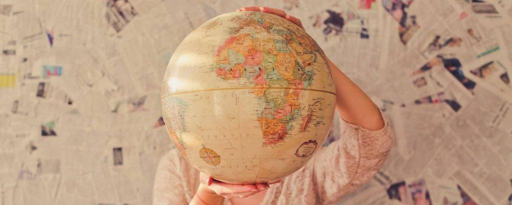 hands carry world map beside newspaper