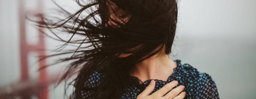 woman hand on chest hair flying covering face