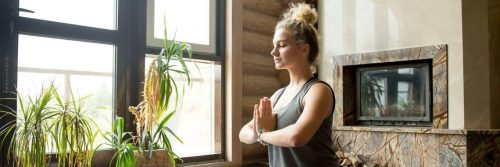 woman eyes closed meditate beside plant pots heaters in quiet peaceful living room