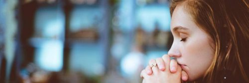 woman holds hand closed eyes thinking