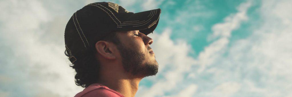 man eyes closed wears black cap meditating in blue cloudy sky