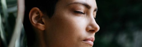woman closing eyes focuses on breathing eliminating negative thoughts