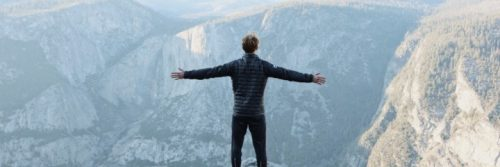 man stands on mountain top facing backward gratitude life