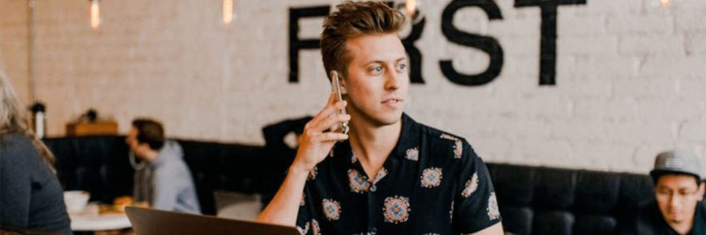 man sits in busy coffee shop answering phone
