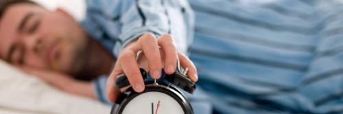 man sleeps while holding clock