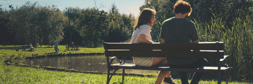 couple sits on bench opposite to lake in park talking