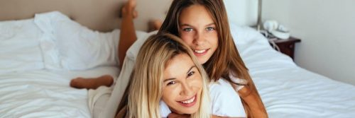 woman lies upside down on bed smiling while daughter lying on mom smiling