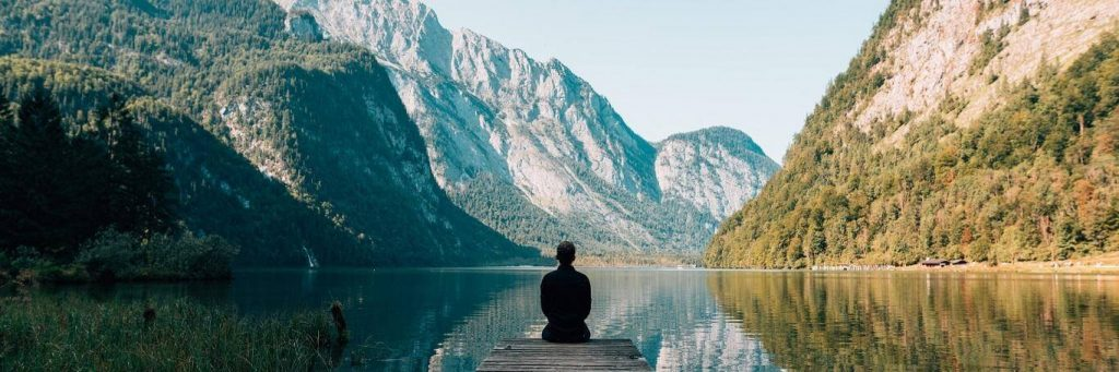 man sits on cliff facing backward looking at breakthrough mountain in blue clear sky