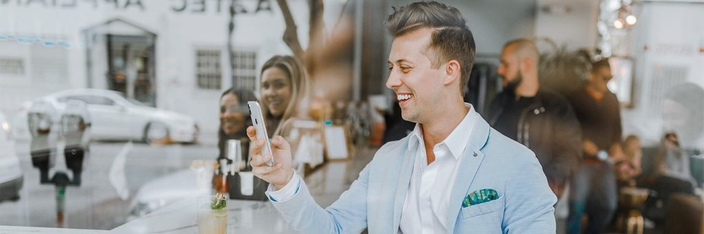 businessman stands outside crowded shop talking on phone smiling happily