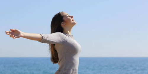 woman stands beside blue ocean closed eyes gratitude life in blue clear sky