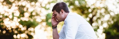 man sits hand in face feeling sad worried painful overthinking