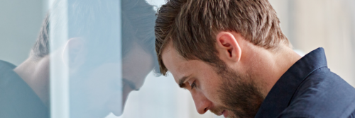 man stands head on glass feeling depressed sad exhausted tired