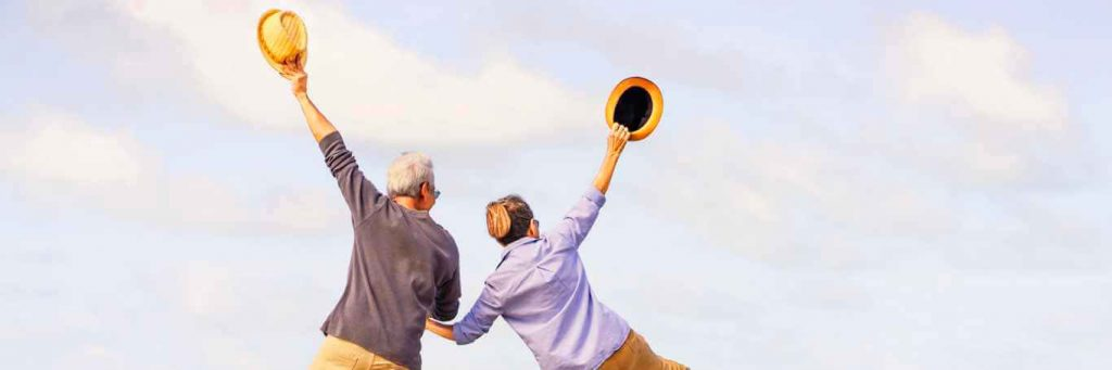 couple hand in hand stands backward raises hands holding yellow hat
