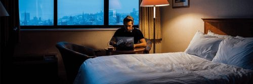 man sits beside bed in bedroom working on laptop on side table at late night