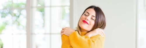 woman wearing yellow sweatshirt satisfied hugging herself in living room