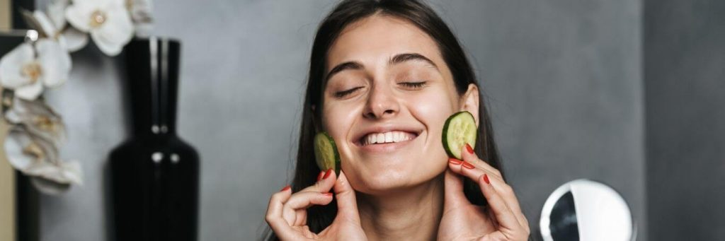 woman eyes closed happily apply cucumber slices on face skin