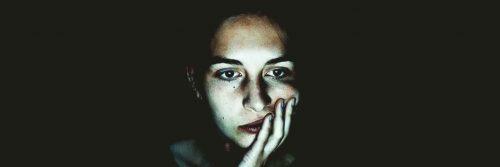 woman sad depressing face hand in face upset in dark