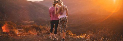 two women stand on rock side by side facing backward enjoying beautiful sunny weather