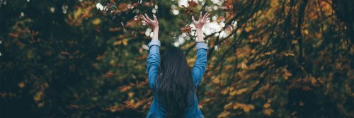 woman stands in forest facing backward gratitude life