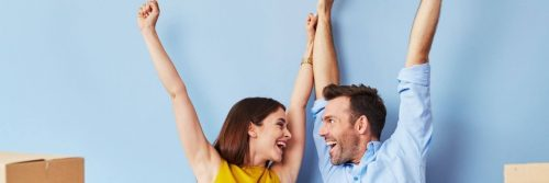 couple happily raises hands looking at each other blue wall