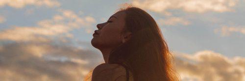woman eyes closed focuses on breathing in blue cloudy sky