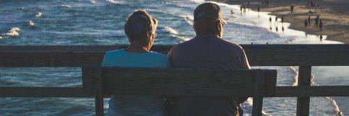 elderly couple sits on bench near beach facing backward enjoying cool weather watching people swimming