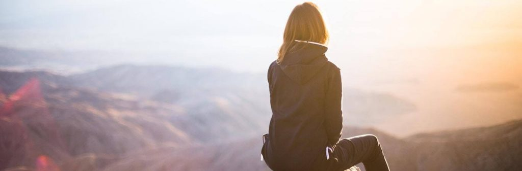 woman facing backward sits on mountain top looking at sunny sky