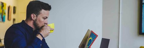 man sits in office drinking in yellow mug while reading book