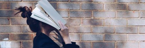 woman holds book covering face stands beside stone wall