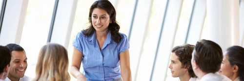 woman stands discussing with colleges in co working room
