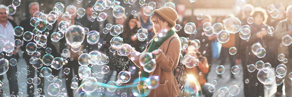 woman stands on street between crowds enjoying bubbles