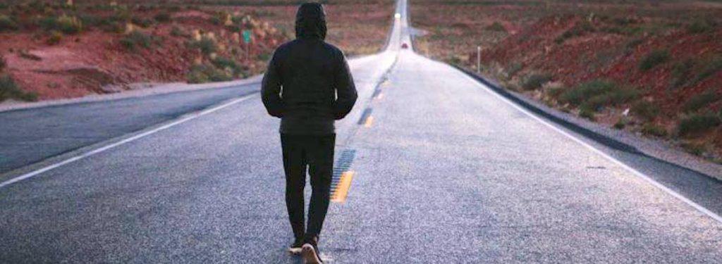 man wearing black hoodie facing backward walks alone on road between mountain