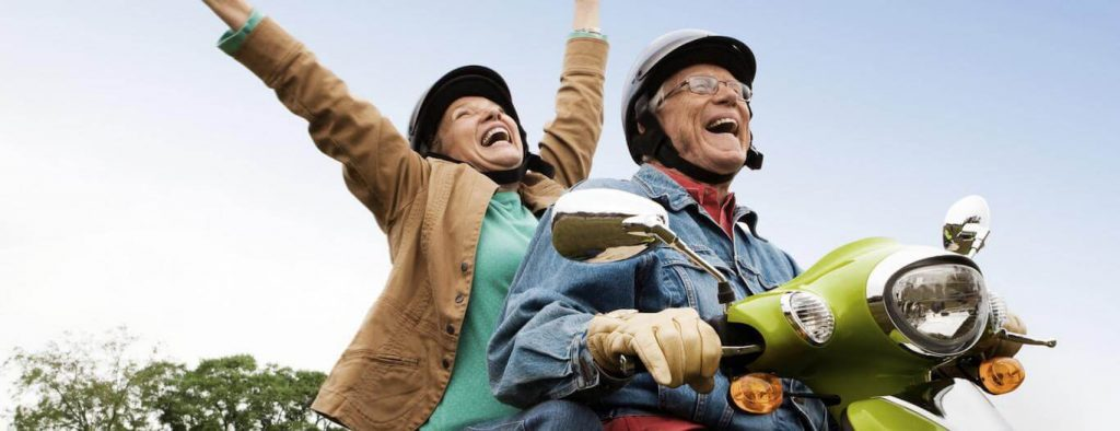elderly couple rides scooter happily laughs while woman sitting behind raising hand