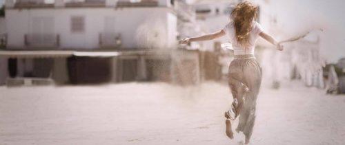 woman facing backward runs on sandy dusty street