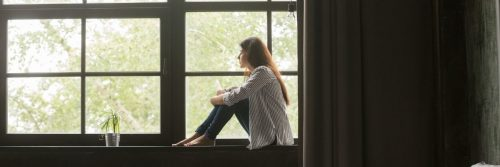 woman sits alone on bench beside window curtain looking outside