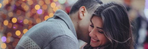 man kisses girlfriend on neck while girl happily smiles