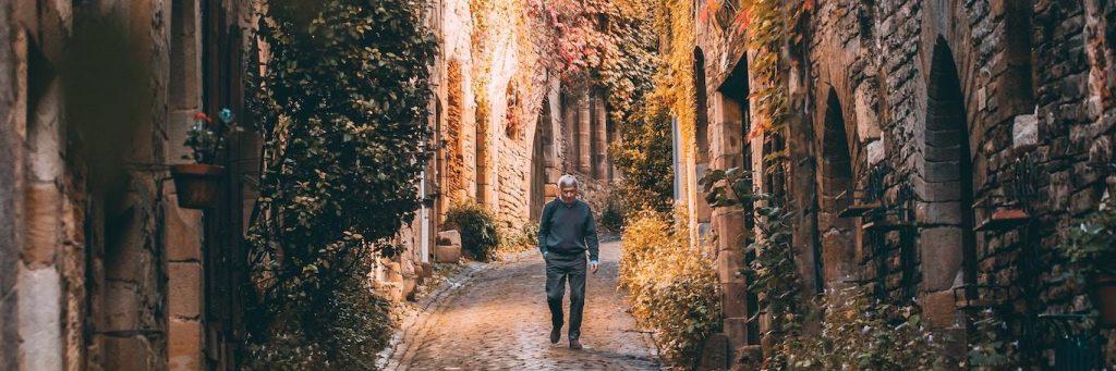 elderly man hand in pocket walks alone along footpath between old buildings