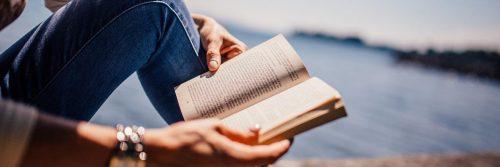 hands holding reading book beside blue ocean