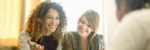 two women sits happily respectfully talking smiling at man