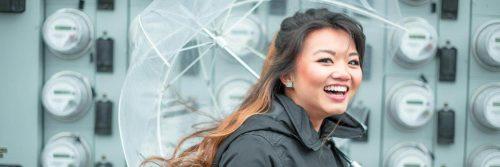 woman carries umbrella happily smiles