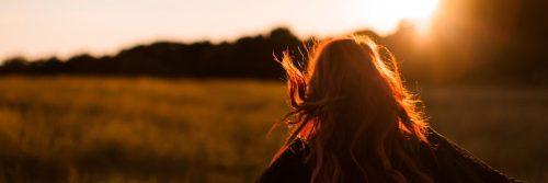 woman facing backward walks on field in sunny sky