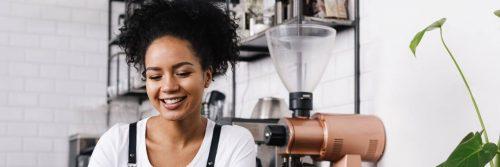 curly black hair woman sits in coffee shop beside coffee machine black shelf happily smile