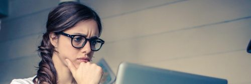 woman focuses on working on laptop in office