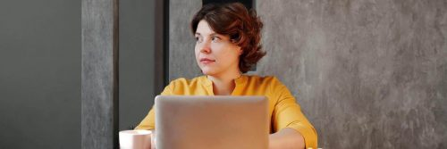 woman wearing yellow long sleeved shirt sits working on laptop looking aside