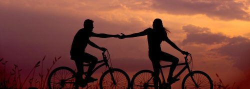 couple shadow rides two bikes hand in hand in beautiful sunset