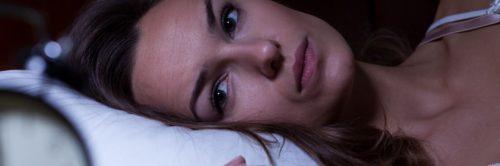 woman stays awake at night having trouble of falling asleep