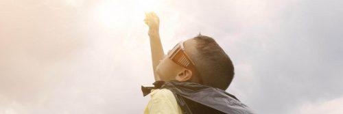 man wearing sunglass raises hand in sunny sky