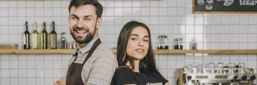 bartender couple standing back to back smiling in coffee shop