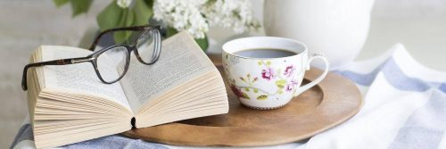 book and white flowerful black prescription glasses on small timber table